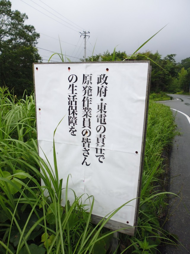 Poster near hotels in Hirono in the middle of the countryside, reading 'It is the responsibility of the government and TEPCO to guarantee the quality of life of everyone working at the nuclear power plant' or words to that effect.